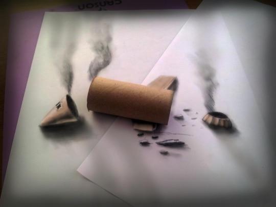 Un rouleau de papier toilette vide posé sur deux feuilles de dessin, des morceaux de fusée font croire à une fusée explosée.