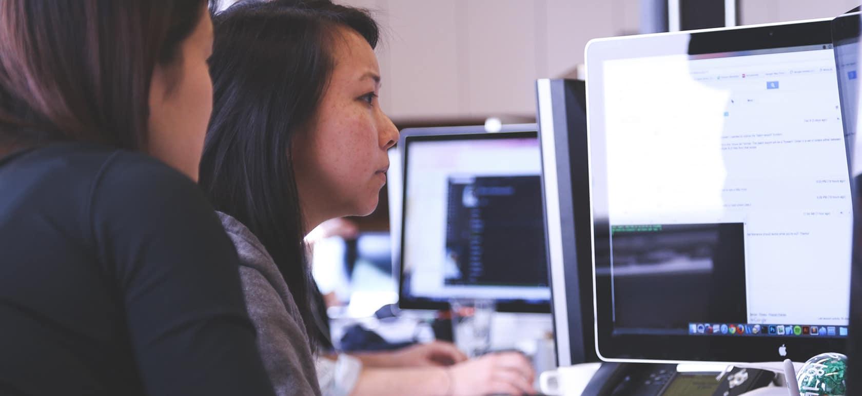 Une femme regardant une autre femme travailler.